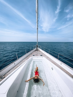A charming slender woman swims in the pool located on the yacht