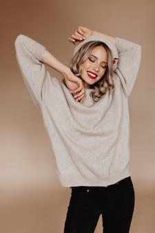 Affascinante signora sottile in maglione marrone che ride con gli occhi chiusi