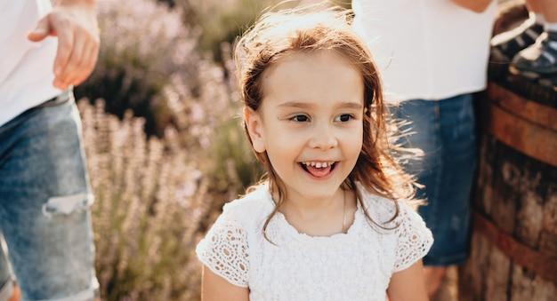 母の日を一緒に過ごす白いドレスを着て両親の近くのフィールドで外でポーズをとる魅力的な小さな白人の女の子