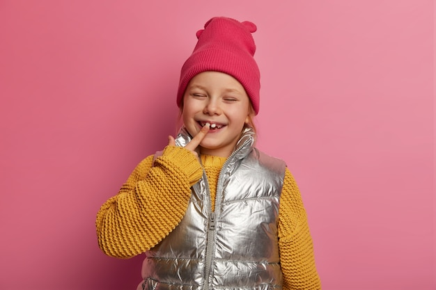 Charming small daughter, little female child indicates at her new tooth, smiles broadly, wears hat, knitted sweater and vest, prevents caries, cares about teeth, models over pastel rosy wall