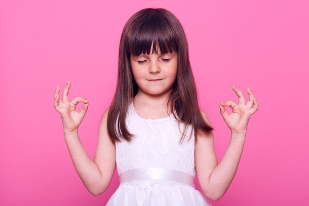 Charming small girl with dark hair wearing white dress keeping eyes closed, relaxing, stands with hands in okay gesture, isolated over pink wall