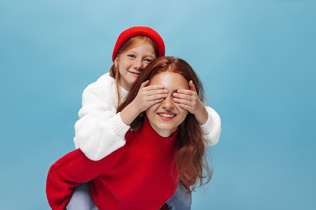 Charming small girl with ginger hair in red cap and white sweater closes eyes her smiling elder sister in bright clothes