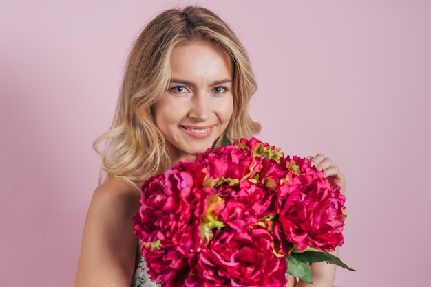 Charming smiling blonde young woman holding flower bouquet against pink backdrop