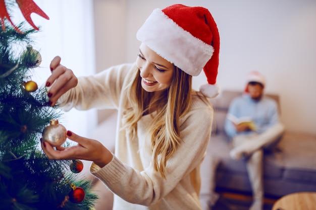 リビングルームに立っている間クリスマスツリーを飾る頭の上のサンタ帽子と魅力的な笑顔白人ブロンドの女性。バックグラウンドで彼女のボーイフレンドは本を読んでいます。