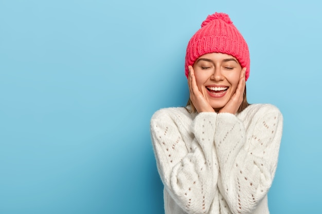 Charming smiling feminine girl touches cheeks with both hands, eyes shut, toothy alluring smile, wears winter white sweater, poses against blue studio wall, has pure healthy skin, feels relieved