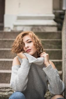 매력적인 웃는 아가씨 스웨터의 칼라를 잡고 계단에 앉아
