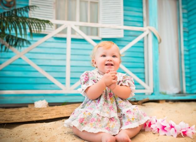 花柄のドレスを着た魅力的な笑顔の少女は、青いカントリーハウスを背景に砂の上に座っています。
