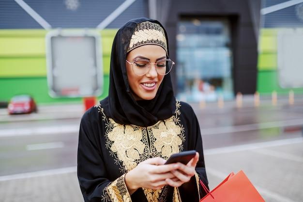 伝統的な服装で魅力的な笑顔のイスラム教徒の女性が手に悪い買い物をしてショッピングモールの前に立って、新しいスマートフォンを試します。ミレニアル世代。多様性の概念。