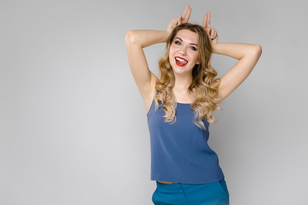 Charming smiling young blonde girl in blue clothes showing funny gesture on gray