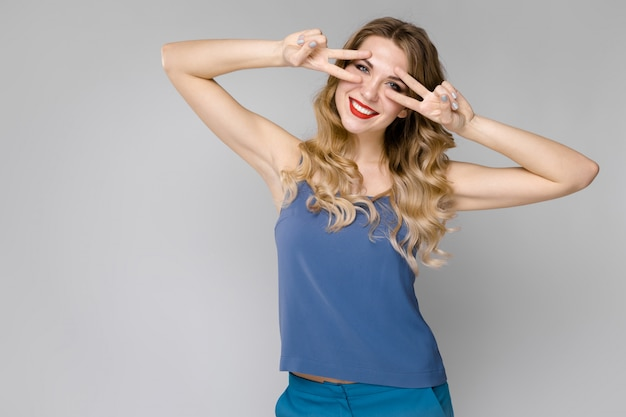 Charming smiling young blonde girl in blue clothes showing funny gesture  gray