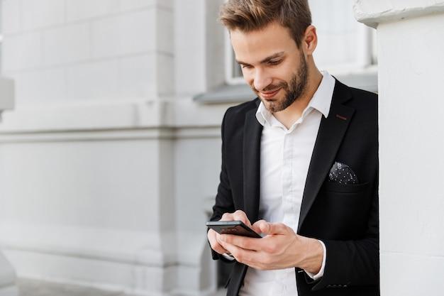 Очаровательный улыбающийся молодой бизнесмен в костюме, стоящий в городе, с помощью мобильного телефона