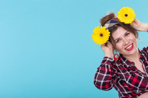 파란색 표면에 포즈를 취하는 그녀의 손에 밝은 노란색 꽃을 들고 격자 무늬 셔츠에 매력적인 웃는 젊은 긍정적 인 여자