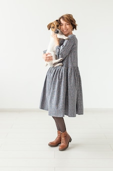 Charming smiling young woman in a stylish gray dress holding her favorite dog jack russell terrier