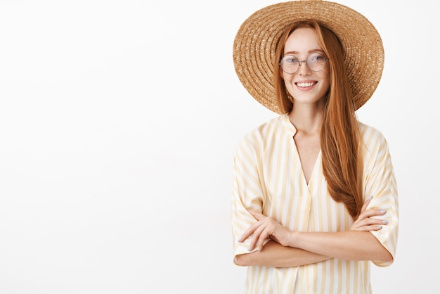 Charming sociable and creative female explorer in yellow striped blouse straw hat and trendy glasses holding hands crossed on chest and smiling with carefree and relaxed expression