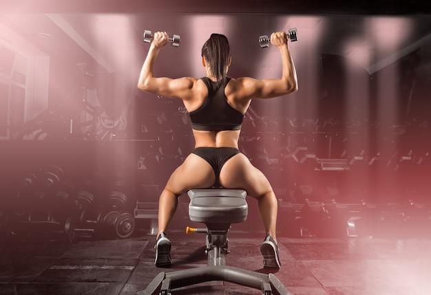 Очаровательная спортсменка выполняет упражнение с гантелями. вид сзади. смешанная техника