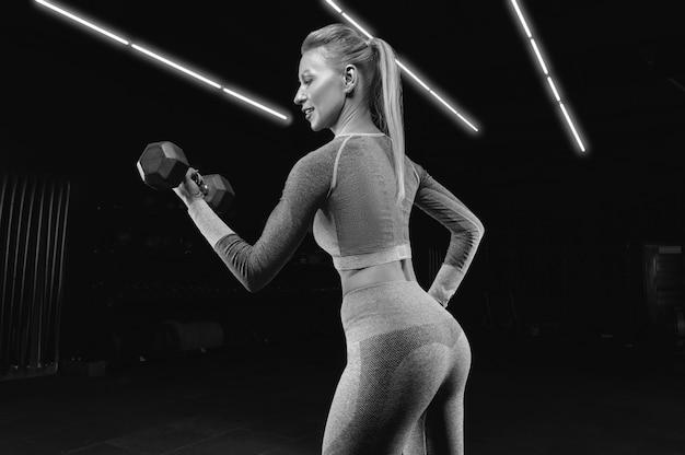 Очаровательная спортсменка позирует в тренажерном зале с гантелями. понятие о бодибилдинге, фитнесе, растяжке, здоровом питании. смешанная техника