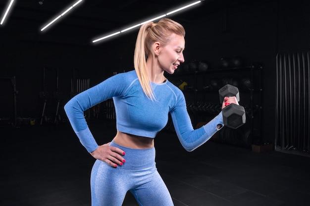 아령과 체육관에서 포즈 매력적인 sportswoman. 보디 빌딩, 피트니스, 스트레칭, 건강한 식습관의 개념. 혼합 매체