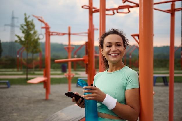 魅力的なスポーティな成熟したアフリカ系アメリカ人女性は、朝のトレーニングの後に残りを楽しんで、歯を見せる笑顔で笑って、スマートフォンでモバイルアプリケーションをスワイプし、彼女の体を水分補給するために水を飲みます