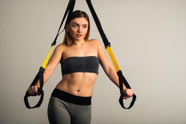 スポーツウェアの魅力的なスポーティな若い女性のフィットネスモデルは、彼女の手で吊りストラップを保持します