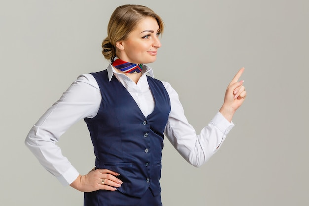 Charming stewardess dressed in blue uniform pointing the finger on gray