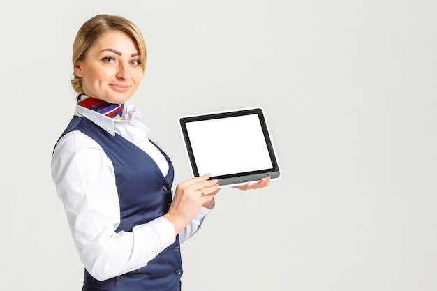 Charming stewardess dressed in blue uniform with empty blank in hands