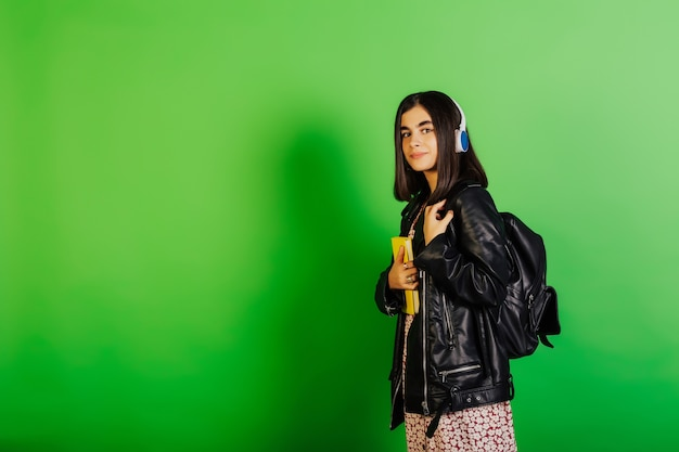 ドレス、革の黒いジャケット、黒いバックパックの魅力的な学生は、黄色のノートブックを持って、ワイヤレスヘッドフォンで音楽を聴いています。
