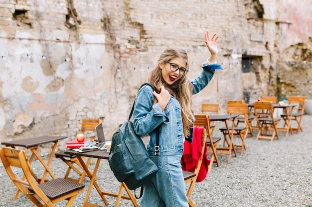 Charming student passed exams perfectly. adorable girl in a fashionable denim suit leaves the outdoor cafe and says goodbye to friends.