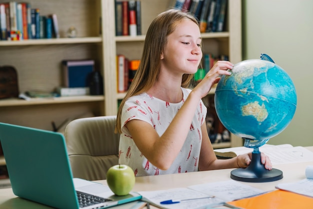 Charming student working with globe at desk