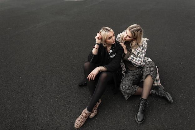 街の路上でアスファルトの上で休むクールな若者の靴のファッショナブルなジャケットを着た魅力的なスタイリッシュなガール フレンド。屋外に座っているトレンディな服を着た美しい 10 代の少女