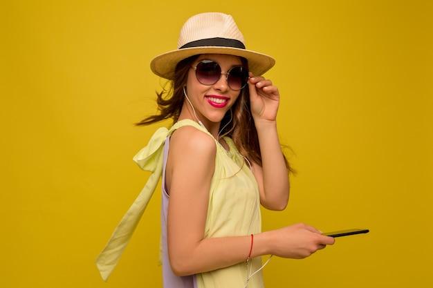 Affascinante donna elegante con gli occhiali e cappello con lo smartphone