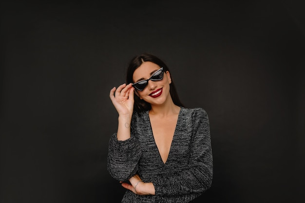 Charming stylish woman with red lips holding her glasses and smiles