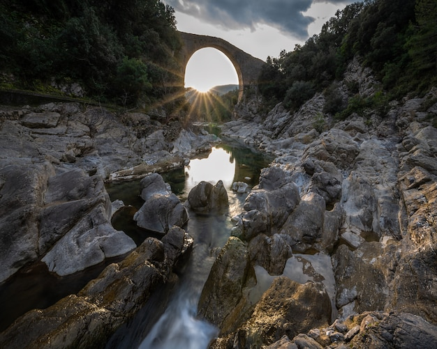 Charming sunset sun stars inside a bridge behind a small river surrounded by rocks with reflected warm light in spain