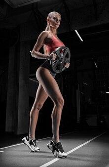 Очаровательная высокая спортсменка позирует в тренажерном зале с гантелями. понятие о спорте, бодибилдинге, фитнесе, аэробике, растяжке.