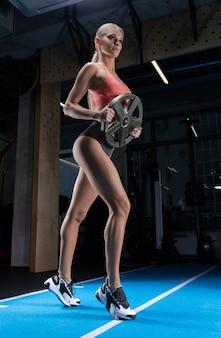 무게 플레이트와 체육관에서 포즈 매력적인 키가 선수. 스포츠, 보디 빌딩, 피트니스, 에어로빅, 스트레칭의 개념.