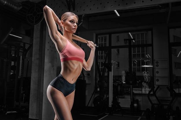 체육관에서 포즈 매력적인 키가 sportswoman. 스포츠, 보디 빌딩, 피트니스, 에어로빅, 스트레칭의 개념.