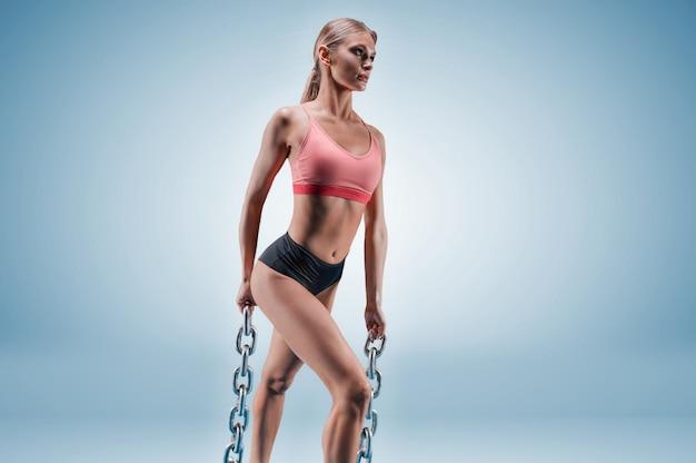 彼女の手に鎖を持つ青い背景のスタジオでポーズをとる魅力的な背の高いスポーツウーマン。スポーツ、ボディービル、フィットネス、エアロビクス、ストレッチのコンセプト。
