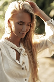 흰색면 블라우스에 매력적인 검게 그을린 매력적인 여자는 외부 닫힌 눈으로 포즈