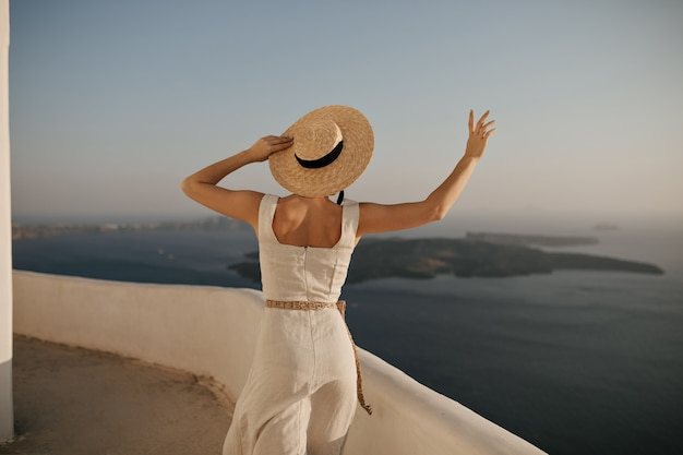 Очаровательная загорелая женщина в бежевом платье и соломенной шляпе гуляет по морской стене