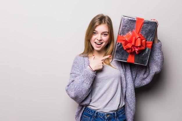 Affascinante ragazza adolescente che punta alla confezione regalo con il suo dito isolato su bianco