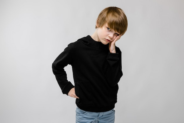 Charming teenager with blond hair and dark eyes. the teenager propped his cheek with his fingers. the teenager is displeased