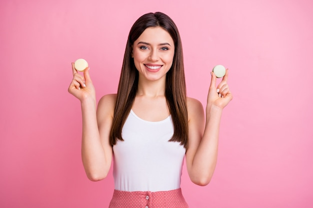 Charming tempting lady hold two tasty macaron cookies