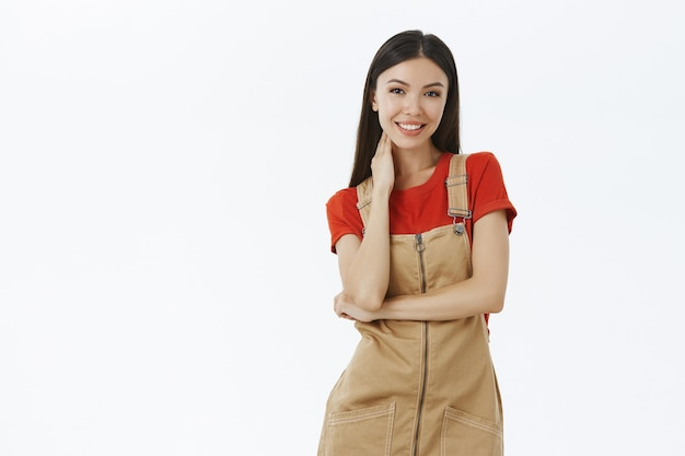 Charming tender asian girl in brown overalls over red t-shirt touching neck gently being shy and awkward