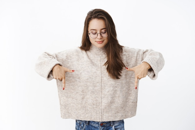 Charming tender and cute young female brunette in transparent glasses and sweater tilting head looking and pointing down with interest and delight smiling broadly as observing curious copy space.