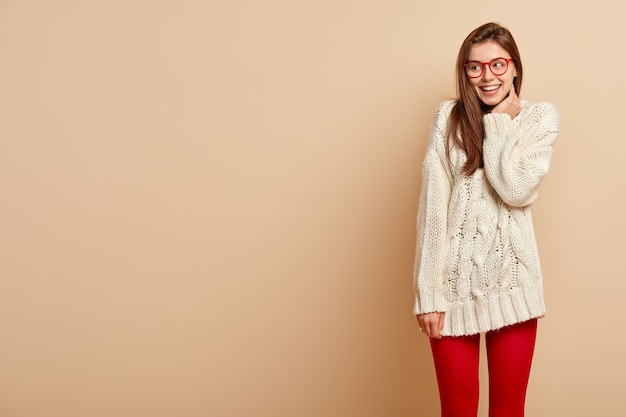 Affascinante ragazza femminile tenera esprime atteggiamento ottimista e felicità, sorride con gioia, concentrata da parte