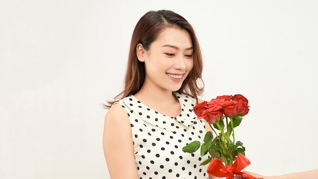 매력적인 부드러운 소녀는 빨간 장미를 손에 들고 사려 깊게 옆을 바라보고 있습니다. 흰색 배경에 사진입니다.