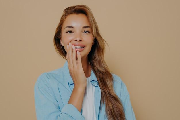 Очаровательная нежная женщина нежно трогает щеку рукой на фоне студии