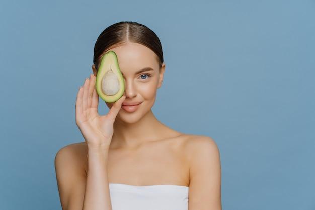 Очаровательная нежная женщина с зачесанными темными волосами со светящейся кожей покрывает глаза половинкой авокадо.
