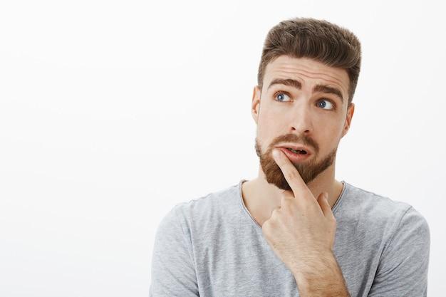解決策を考えようとしている魅力的な思慮深い、カリスマ的な男。ひげと青い目をした創造的なハンサムな黒髪のボーイフレンドは、唇に触れて左上隅を見て眉を上げて眉毛を考えて