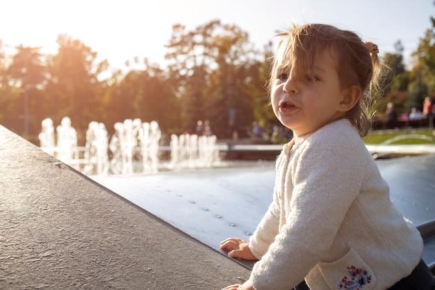 魅力的な幼児の女の子は、公園を背景に顔としかめっ面を作ります。子供は元気に遊んでいます。幸せな子供時代
