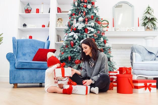彼女の母親が休日の贈り物を開梱して魅力的な幼児。